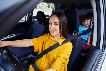 Woman driving a car, child behind