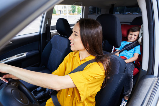 Nice woman driving car with son sitting in baby seat