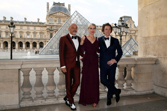 Shoe designer Christian Louboutin and actress Melita Toscan du Plantie pose as they attend the charity dinner of the American Friends of the Louvre, at the Louvre museum in Paris
