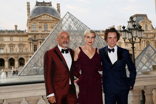 Shoe designer Christian Louboutin and actress Melita Toscan du Plantier pose as they attend the charity dinner of the American Friends of the Louvre, at the Louvre museum in Paris
