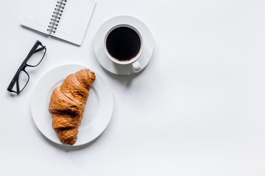 Businessman morning with notebook, cup of coffee and croissant on wooden table background top view mockup