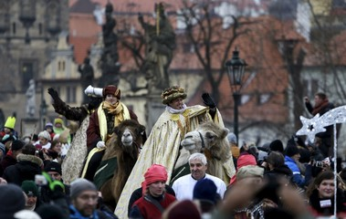 Men dressed as the Three Kings greet spectators as they ride camels during the Three Kings procession across the medieval Charles bridge in Prague