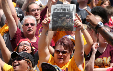 A Cleveland Cavaliers fan celebrates while holding up the front page of a newspaper as the Cavaliers team plane arrives home to a welcome party in Cleveland