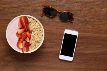 Bowl of muesli and smartphone on a wooden table.