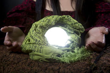 Fortune tellers hands or psychic over a glowing crystal ball.  The occult object has a mysterious magical light.  The image depicts pagan spirituality or superstition and witchcraft.