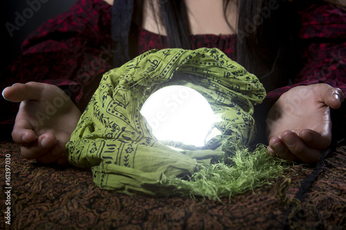 Fortune tellers hands or psychic over a glowing crystal ball