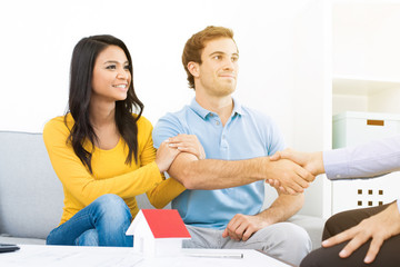 Young couple meeting with real estate agent at home