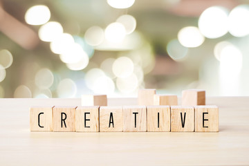Creative word on wooden cubes over blur background, success in business concept