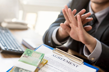Businessman refusing money that come with agreement paper