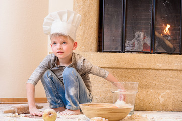 A boy in chef's hats near the fireplace sitting on the kitchen floor soiled with flour, playing with food, making mess and having fun