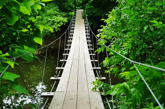 Small wood pedestrian suspension bridge with steel cables over a river in the woods