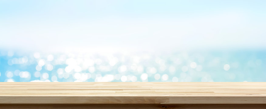 Wood table top on blue summer sparking sea water bokeh banner background