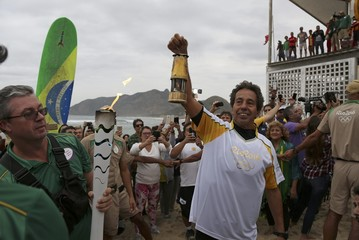 Brazilian surfer Rico de Souza holds up the Olympic torch after surfing with it at praia da Macumba (Macumba beach) in Rio de Janeiro   , Brazil
