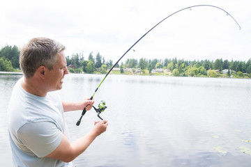 Handsome man fishing at a lake