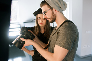 Conflict with photographer on photoshoot. Model didn't like photos on camera. Man with camera show pictures to angry woman in during the studio session.