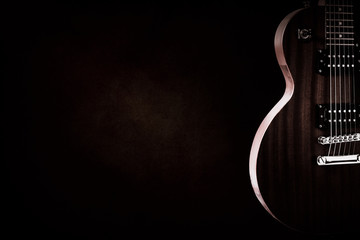 Part of the red electric guitar on black background. A place for writing of the text.