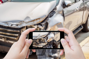 woman using mobile smartphone taking photo of car accident damaged for insurance