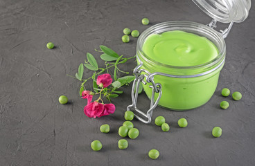Healthy food. Fresh puree of green peas in open glass jar with pink flowers of sweet pea