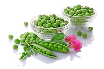Healthy food. Fresh green peas in glass bowls with pink flowers of sweet pea