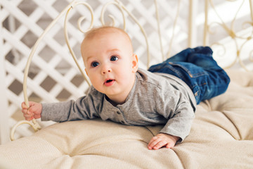 Adorable baby boy in sunny bedroom. Newborn child relaxing. Nursery for young children.Family morning at home. Little kid lying on tummy