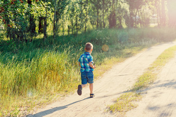 Little boy in a blue plaid shirt and shorts runs on a footpath in the wood