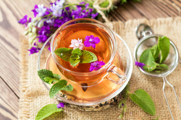 Glass cup of summer herbal tea with fresh mint and field larkspur. Wooden table. Shallow depth of field.