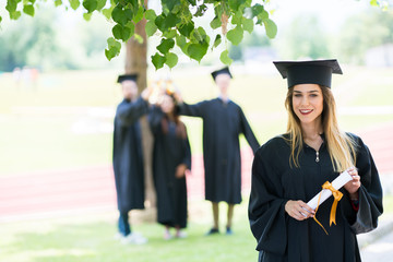 female college student in graduation cap and gown on campus