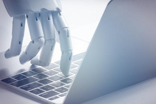 Chat bot , artificial intelligence , robo advisor , robotic concept. Robot finger point to laptop button. Blue tone.