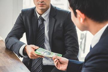 Businessman giving money, Australian dollars, to his partner