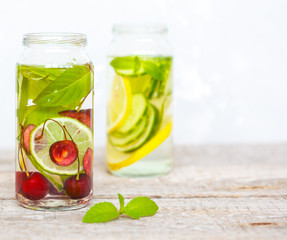 Citrus, cherry and herbs infused sassi water for detox or dieting in glass bottles. Clean eating, weight loss, healthy lifestyle concept