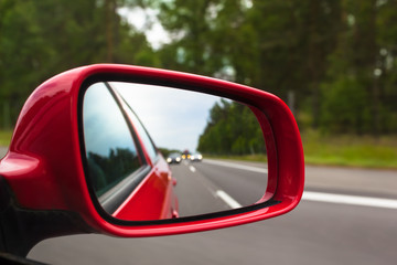 Highway Rear View / View back to road through red side mirror at car