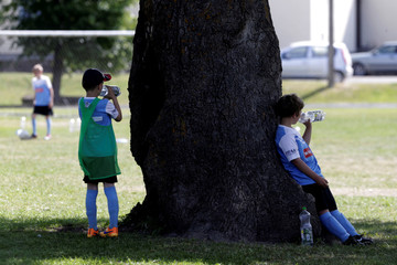 Children rest in the shadow of an oak in the middle of  soccer pitch in Orissaare