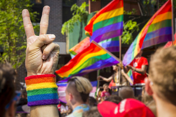 Supporting hands make peace sign in front of a rainbow flags flying on a float of a summer gay pride parade