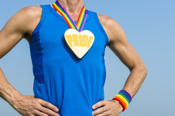 Gay athlete standing with pride heart gold medal and rainbow ribbon against blue sky