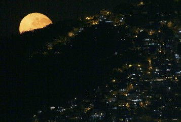 The moon sets behind the Vidigal favela in Rio de Janeiro