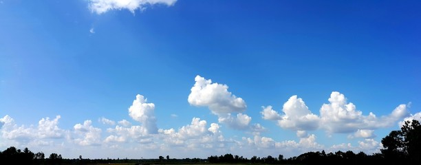 Panorama view of clear blue sky with soft white clouds and sun rays