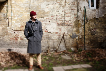 Blurred picture of man in grey coat standing before ruined wall