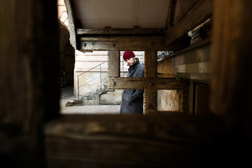 Look through wooden blocks at young man in grey coat