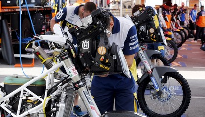 Mechanics of the Husqvarna Racing Team work in the team's box ahead of the Dakar Rally 2016 in Buenos Aires