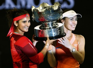 Switzerland's Hingis and India's Mirza pose with the trophy after winning their doubles final match at the Australian Open tennis tournament at Melbourne Park