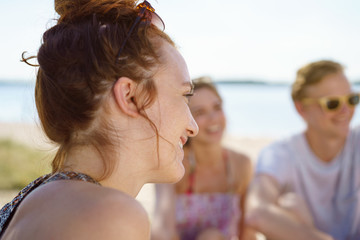 Young woman chatting with friends on the beach