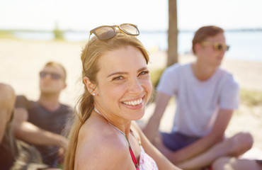 Attractive woman relaxing on a beach with friends