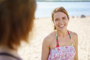Young woman talking with a friend on the beach