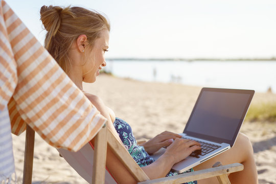Young woman typing on a laptop on a beach