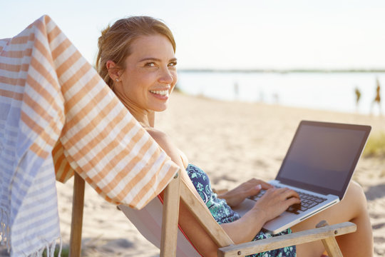 Friendly young woman using a laptop at the beach