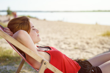 Pretty young woman relaxing on a deckchair
