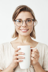 Cute beautiful girl in glasses smiling looking at camera holding cup over white background.