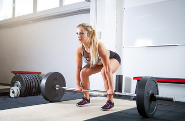 Woman doing deadlift exercise, weight lifting workout at crossfit gym