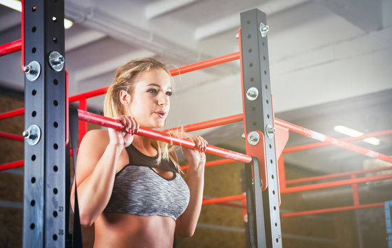 Woman doing pull ups on bar at crossfit gym