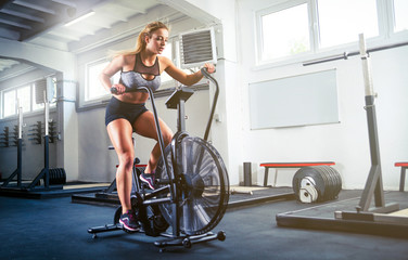 Woman at crossfit gym using exercise bike for cardio workout